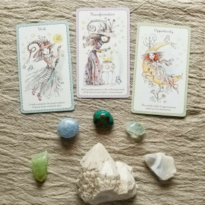 Three Witchinlings cards (wish, transformation, and opportunity) sit above some crystals (green calcide, blue calcite, blue topaz, agate slice, chrysocolla, and pineapple quartz) on a linen cloth